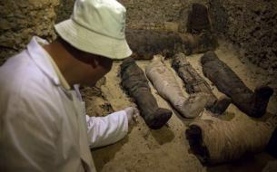 Археолог демонстрирует найденные мумии